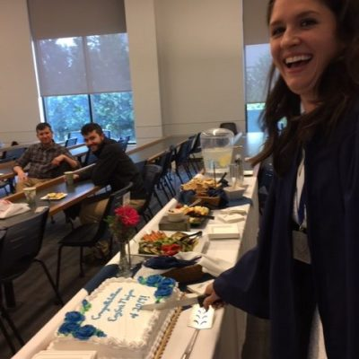 Photo of CogSci graduate cutting cake